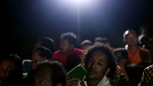 Migrant workers wait for their work permits to checked by Malaysian authorities following a raid at Port Dickson, Malaysia, on July 11, 2017.