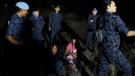 n this picture taken late July 11, 2017, migrant workers sit amidst Malaysian immigration officials in an open field following a raid at a construction site in Port Dickson. Malaysia's immigration department is carrying out a nationwide crackdown on illegal foreign workers after a deadline for registration expired on June 30.