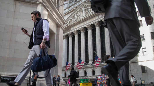 Pedestrians walk past the New York Stock Exchange.