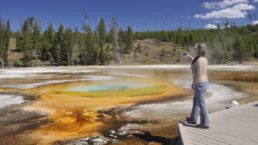A tourist visits the Chromatic Pool at Yellowstone National Park, Wyoming.