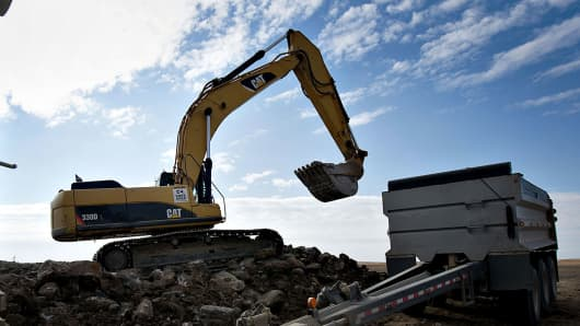 A Caterpillar 330DL track excavator loads rocks for a road construction project.