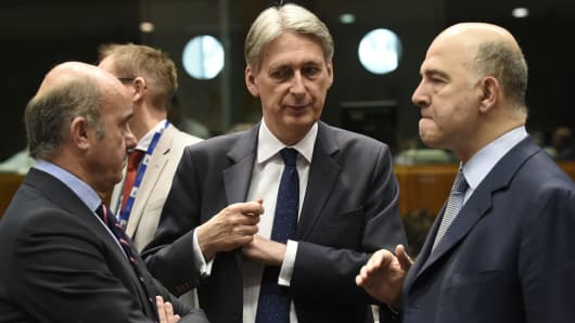 Britain's Chancellor of the Exchequer Philip Hammond (C) talks with EU Commissioner of Economic and Financial Affairs, Taxation and Customs Pierre Moscovici (R) as Spain's Economy Minister Luis de Guindos (L) before a session of the Economic and Financial Affairs, Council (Ecofin) with EU finance ministers on May 23, 2017 at the EU headquarters in Brussels.