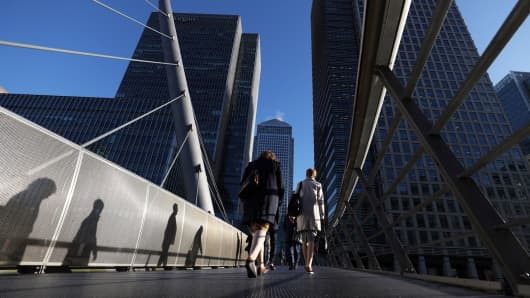 Pedestrians cross a foot bridge towards the offices of global financial institutions, including JPMorgan Chase & Co. and the commercial office block No. 1 Canada Square, in the Canary Wharf financial, shopping and business district in London, U.K.