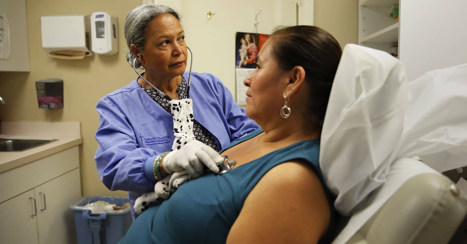 A nurse listens to a client's chest at the Spanish Catholic Center agency of the Diocese of Washington Catholic Charities.