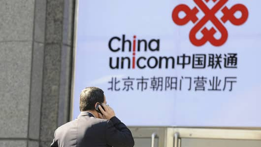 An office worker talks on a mobile phone in front of a China Unicom logo, California-based Apple's partner in China, in Beijing on January 5, 2012.
