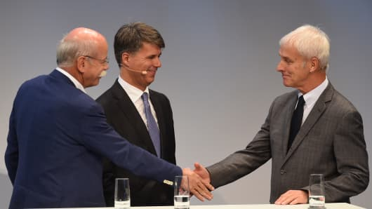 (L-R) Dieter Zetsche, CEO of the German car maker Daimler AG, Harald Krueger, CEO of the German car maker BMW and Matthias Mueller, CEO of German car maker Volkswagen AG, shake hands after a talk at the so-called Auto-Gipfel - automotive meeting - in Munich, southern Germany, on November 9, 2016.