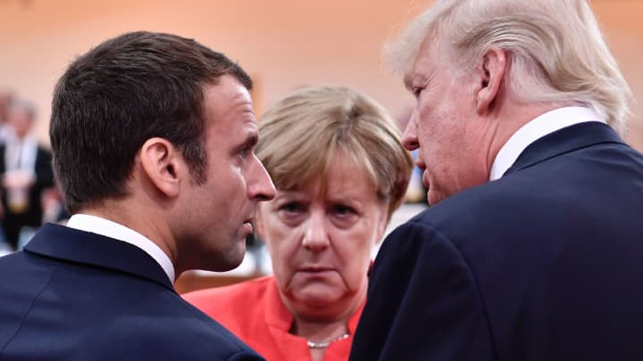 President Donald Trump (R), French President Emmanuel Macron (L) and German Chancellor Angela Merkel (C) chat at the start of the first working session of the G20 meeting in Hamburg, northern Germany, on July 7, 2017.