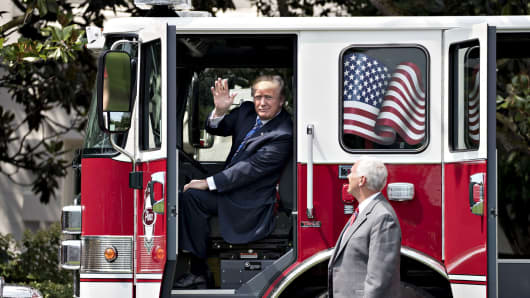 President Donald Trump, center, waves from a fire truck next to U.S. Vice President Mike Pence, right, while participating in a Made in America event, with companies from 50 states featuring their products, on the South Lawn of the White House in Washington, D.C., July 17, 2017.