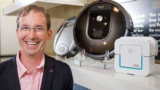 iRobot CEO Colin Angle poses for a portrait with their newest products, the iRobot Roomba 980 and the Braava jet 240, with the original IRobot at far left, at their company headquarters in Bedford, MA.