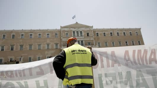 A protestor holds a banner outside the Greek parliament during in a demonstration by municipal contract workers in Athens, Greece, on Thursday, June 29, 2017.