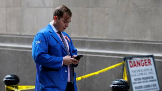 A trader uses his phone outside the New York Stock Exchange (NYSE) in New York.