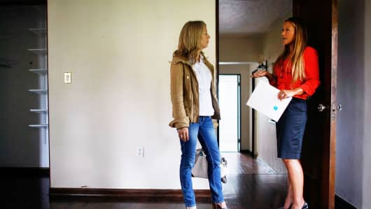 A real estate agent, right, shows a home to a prospective buyer in Miami, Florida.