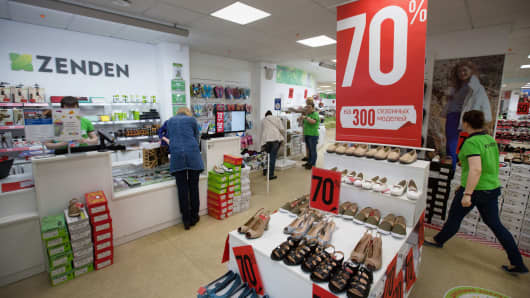 Customers browse discounted shoes inside a Zenden shoe store in Moscow, Russia.