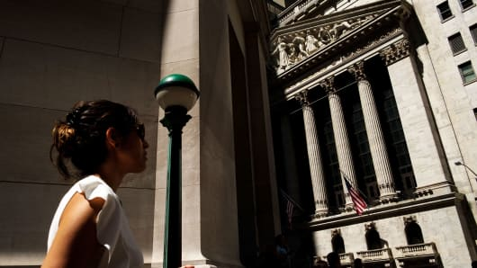 A woman walks past the New York Stock Exchange in New York City.