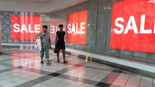 Shoppers walk past sale signs in a mall, White Plains, N.Y.