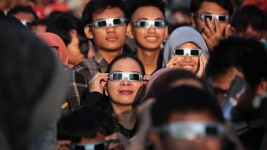 Indonesians use special sunglasses to observe the solar eclipse in Jakarta, Indonesia on March 09, 2016.