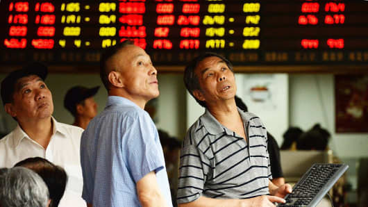Investors gather to check share prices in a security firm in Shanghai on July 28, 2015.