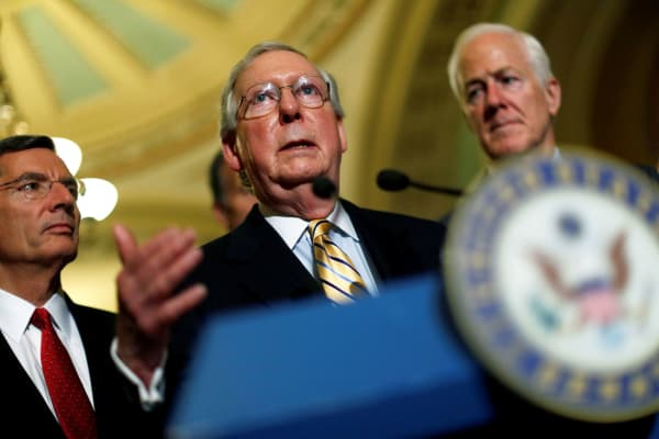Senate Majority Leader Mitch McConnell, accompanied by Senator John Cornyn (R-TX) and Senator John Barrasso (R-WY), speaks with reporters on Capitol Hill in Washington earlier this year.