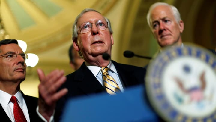 Senate Majority Leader Mitch McConnell, accompanied by Senator John Cornyn (R-TX) and Senator John Barrasso (R-WY), speaks with reporters following the successful vote to open debate on a health care bill on Capitol Hill in Washington, July 25, 2017.