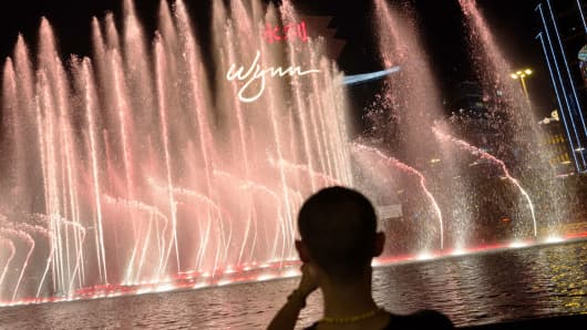 A man takes photographs outside the Wynn Macau casino resort, operated by Wynn Resorts Ltd.