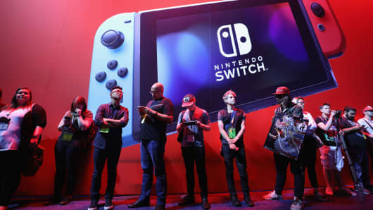 Game enthusiasts and industry personnel walk past the Nintendo Switch exhibit during the Electronic Entertainment Expo E3 on June 13, 2017 in Los Angeles.