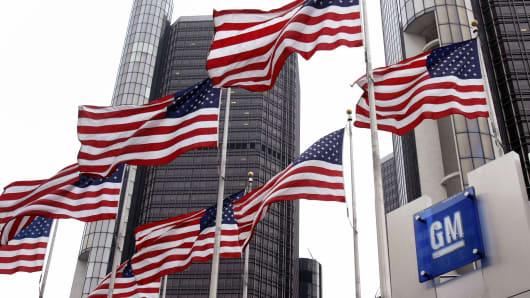 Flags fly outside the General Motors world headquarters building