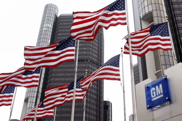 Flags fly outside the General Motors world headquarters building.