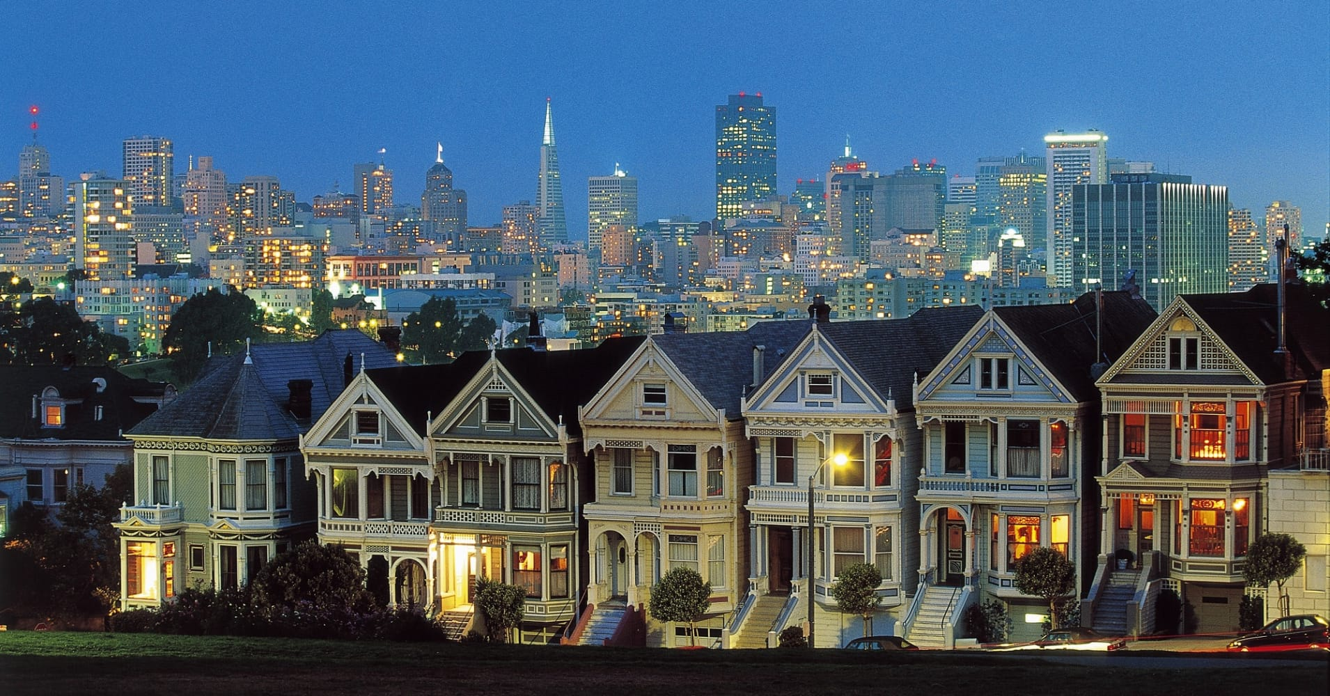 The Painted Ladies, Victorian-style houses with downtown at dusk in the background,