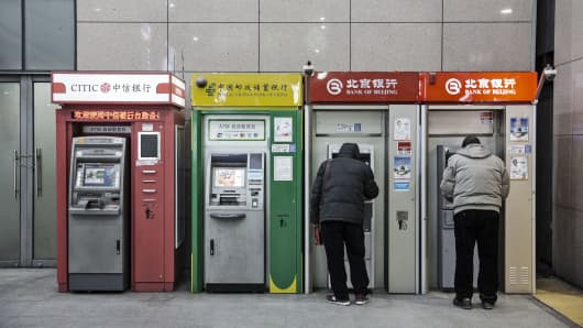 People use automated teller machines (ATMs) in Beijing, China, on Tuesday, Jan. 19, 2016.