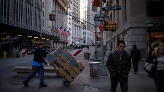 A man pushes a dolly of Amazon.com Inc. boxes as pedestrians walk along Broad Street near the New York Stock Exchange (NYSE) in New York, U.S.