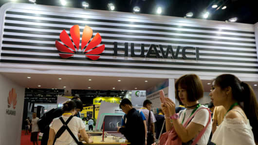 People try using Huawei smartphones at an exhibition.