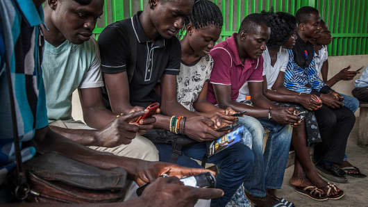 Customers sit and use their mobile phones while waiting to board a ferry in Abidjan, Ivory Coast, on August 31, 2015.