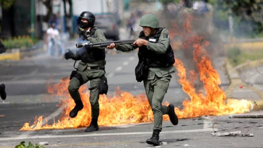 A riot security force member aims his weapon at a rally during a strike called to protest against Venezuelan President Nicolas Maduro's government in Caracas, Venezuela, July 27, 2017.