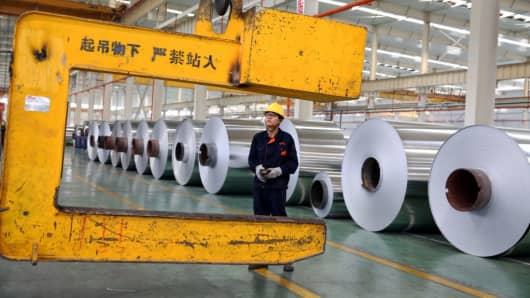 A Chinese worker loading aluminium tapes at an aluminium production plant in Huaibei, east China's Anhui province.