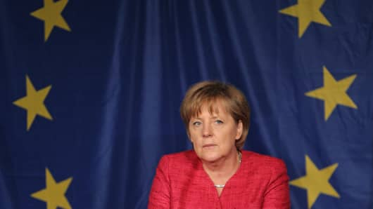 German Chancellor Angela Merkel sits in front of a flag of the European Union