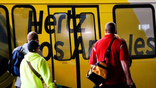 Passengers wait to get on a Hertz shuttle bus at Los Angeles International Airport.