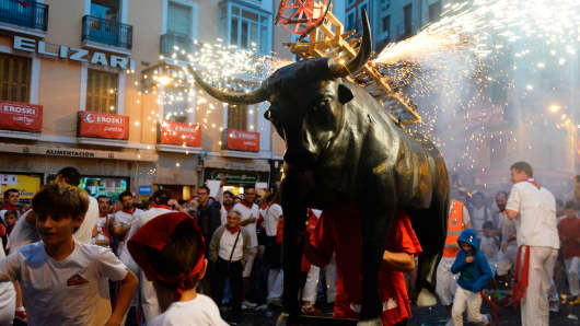A man incarnating a 'Toro de Fuego' (bull of fire) chases people during the San Fermin Festival on July 8, 2017, in Pamplona, Spain.