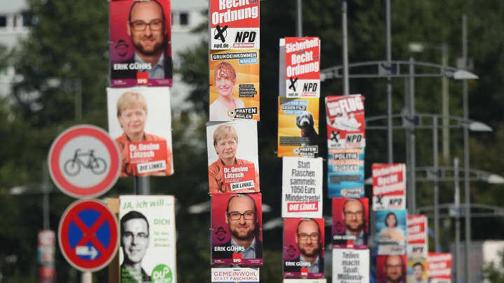 Cars drive past election campaign posters hanging from lampposts on August 22, 2013 in Berlin, Germany.