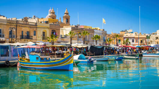 Marsaxlokk market with traditional Luzzu fishing boats in Malta.