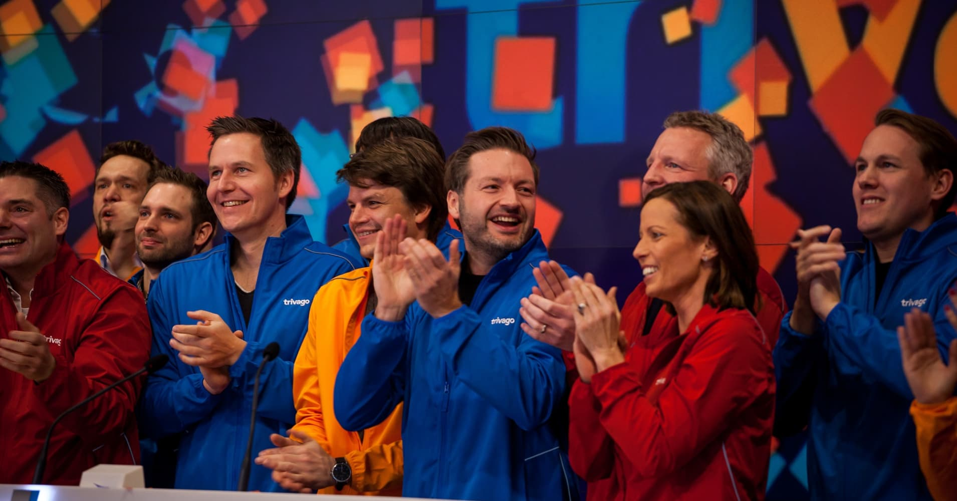 Rolf Schroemgens, co-founder and chief executive officer of Trivago GmbH, center, and employees clap during the opening bell ceremony at the Nasdaq MarketSite during the company's initial public offering.