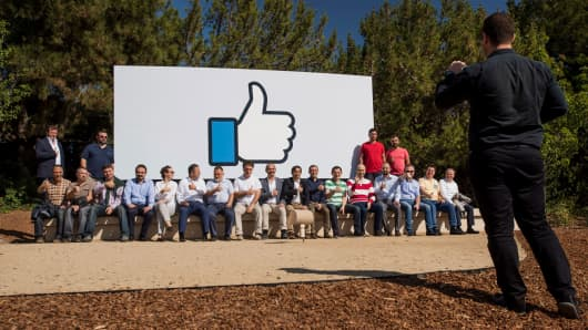 A group of visitors sit for a photograph in front of the 'Like' logo displayed at the entrance of Facebook headquarters in Menlo Park, Calif.