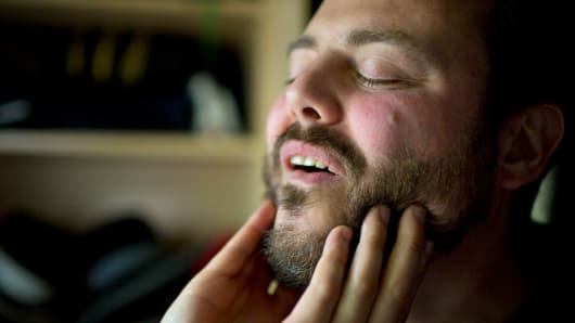 A man applies Urban Beard oil.