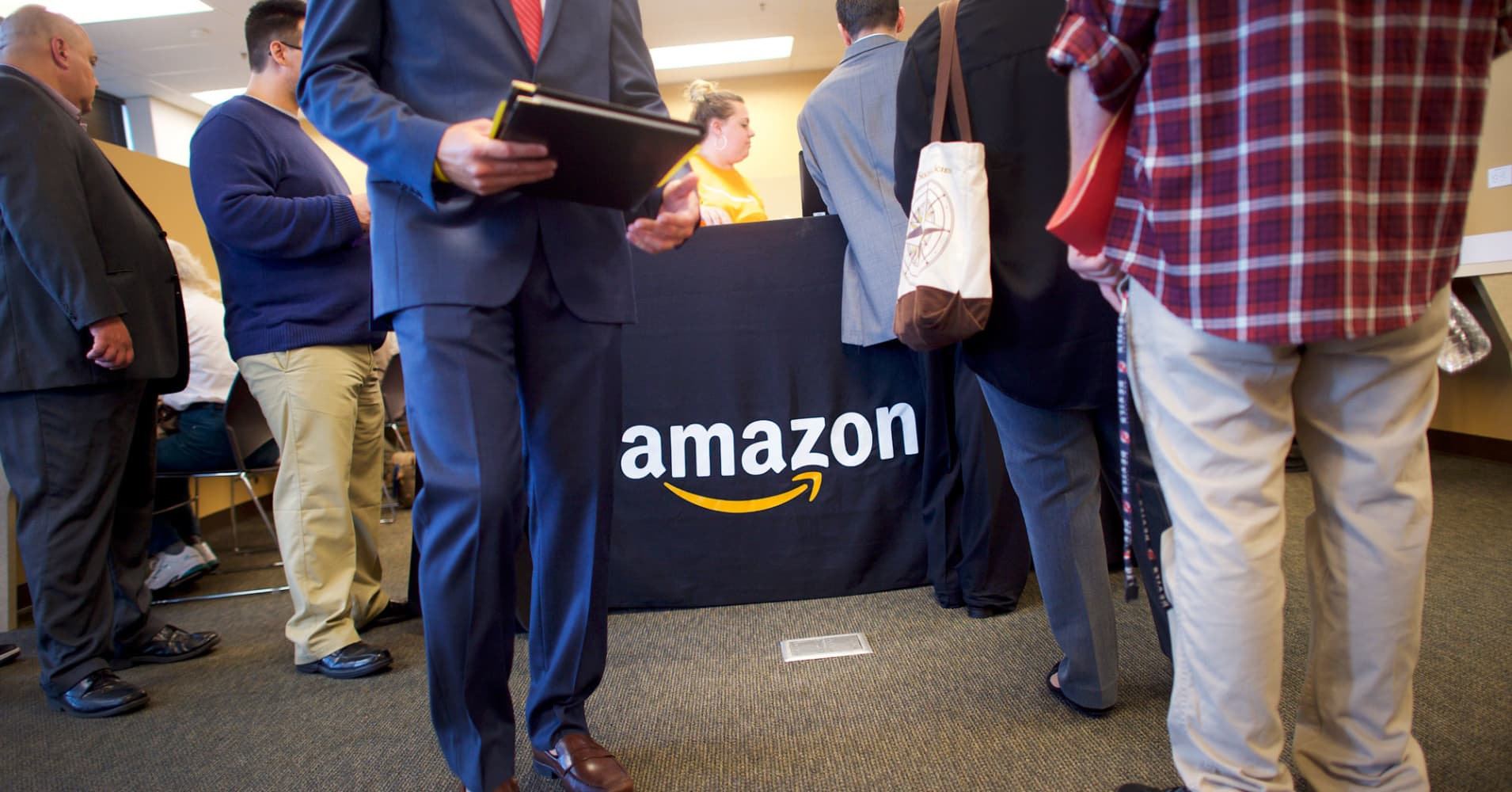 Job seekers register before interviews during an Amazon jobs fair at the Amazon Fulfillment Center on August 2, 2017 in Robbinsville, New Jersey.