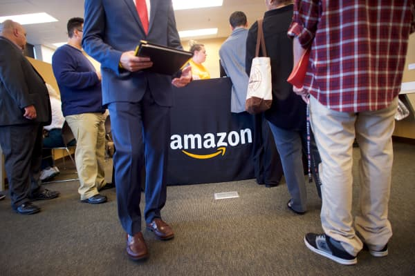Job seekers register before interviews during an Amazon jobs fair at the Amazon Fulfillment Center in Robbinsville, New Jersey.