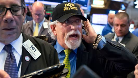 "Trader Peter Tuchman, center, wears a ""Dow 22,000"" hat as he works on the floor of the New York Stock Exchange, Wednesday, Aug. 2, 2017."