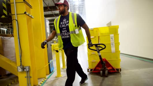 A worker pulls a fork lift at the Amazon Fulfillment Center on August 1, 2017 in Robbinsville, New Jersey.