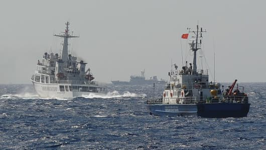 A Chinese coast guard vessel is followed by a Vietnamese coast guard ship in the disputed waters of the South China Sea on May 14, 2014.