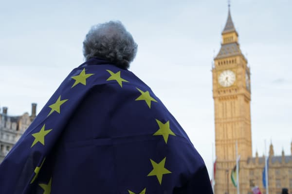 A protester draped in a European Union flag takes part in a protest in support of an amendment to guarantee legal status of EU citizens, outside the Houses of Parliament in London on March 13, 2017.
