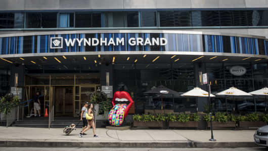 Pedestrians pass in front of a Wyndham Grand Chicago Riverfront Hotel in downtown Chicago, Illinois.