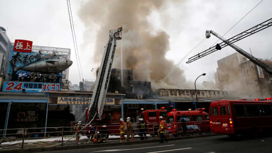 Firefighters operate at the fire site at Tokyo's Tsukiji fish market.